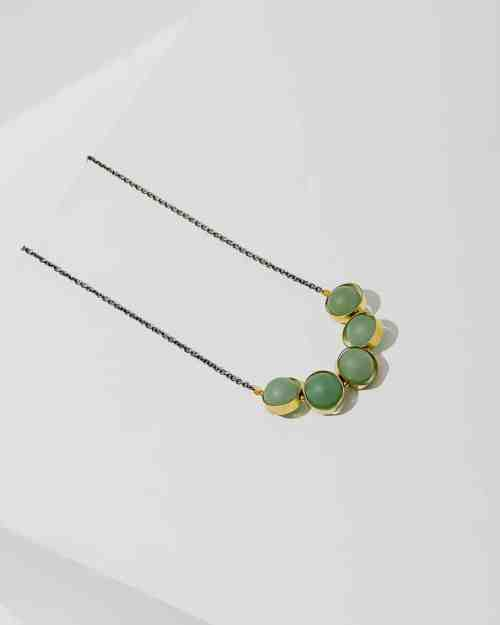 A gold chain necklace with green adventurine stones on the end