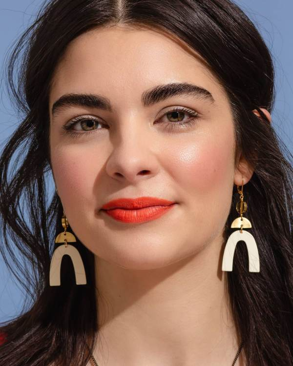 A woman wearing brass earrings with white pendants hanging from them