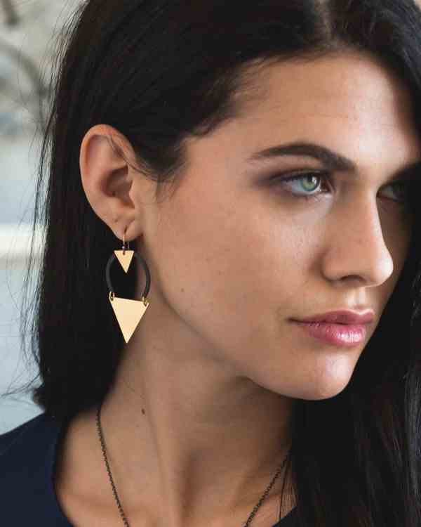 a woman wearing brass earrings with black accents