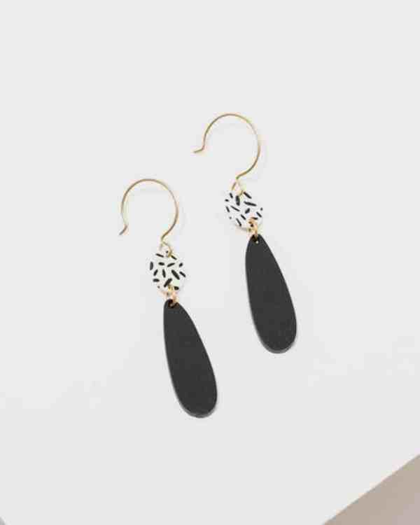 Brass earrings with black pendants hanging from them