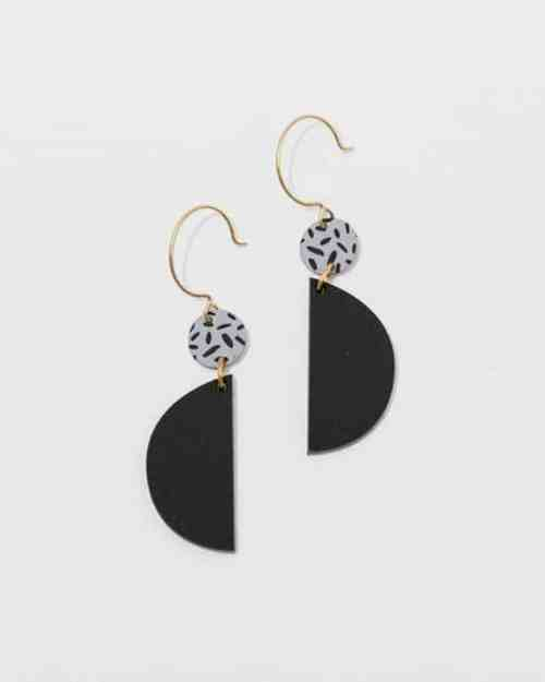 brass earrings with black half circles hanging from them