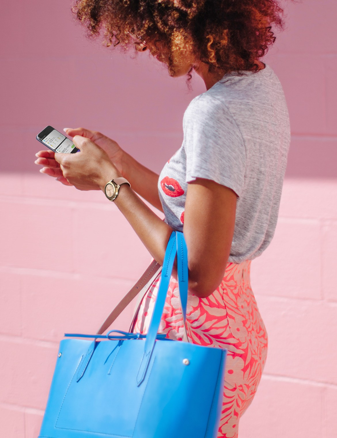 Left side of a woman in white holding a pink purse on a sunny day, wearing a 42mm Rose Gold  Galaxy Watch on her wrist.