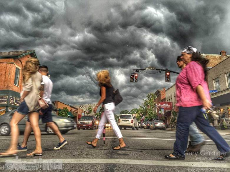 Storm clouds roll over State Street as shoppers rush to their cars.
