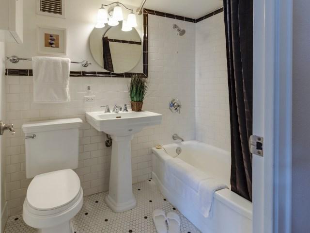 A bath towel, shower curtain, and bath mat in a bathroom.