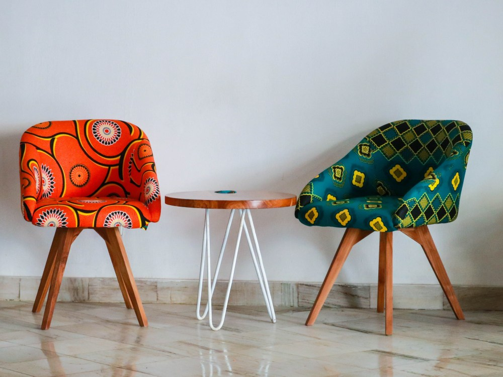 Two chairs with vivid prints aside a table in the middle.