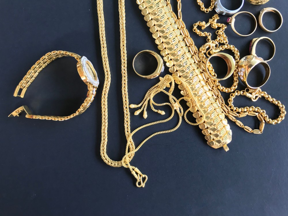 Gold jewelry that includes rings, a watch, necklaces and bracelets.