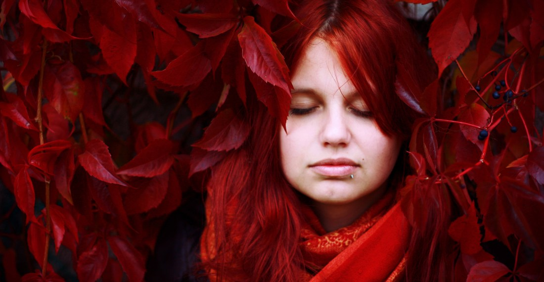 girl with bright red hair against red leaves