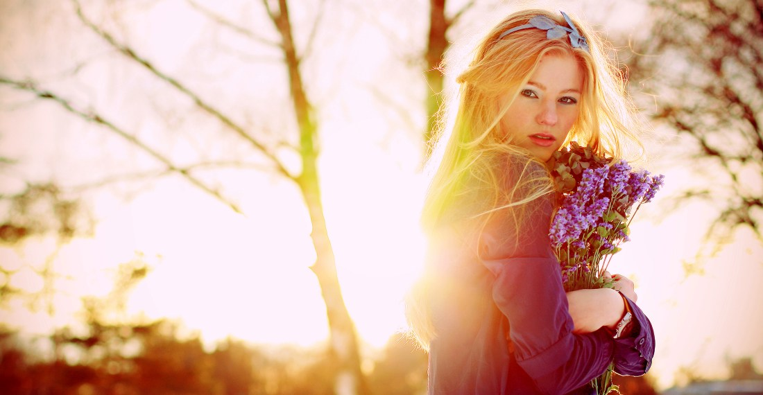 pretty blond girl with flowers in winter forest with sunset behind her