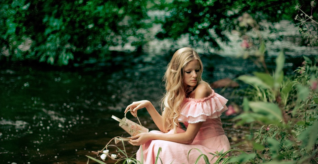 blond girl in a pink dress by a green river