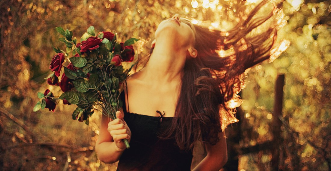 girl with black dress and dark hair with red roses during sunset doing a hair flip