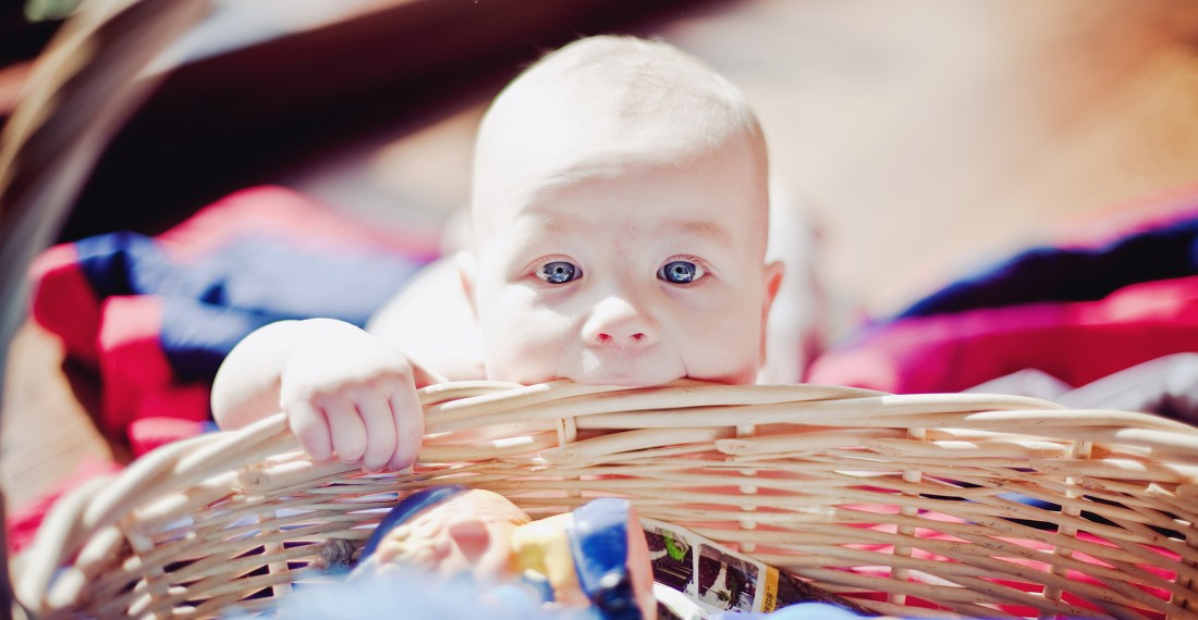 a baby in front of a wicker basket