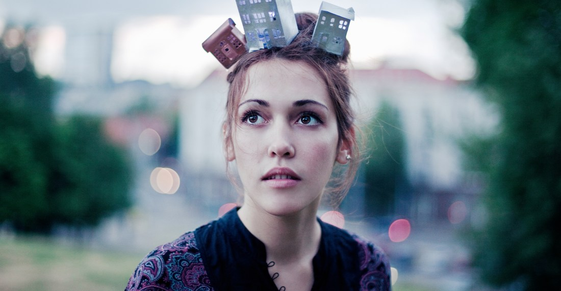 girl with miniature houses on her head and cityscape behind her