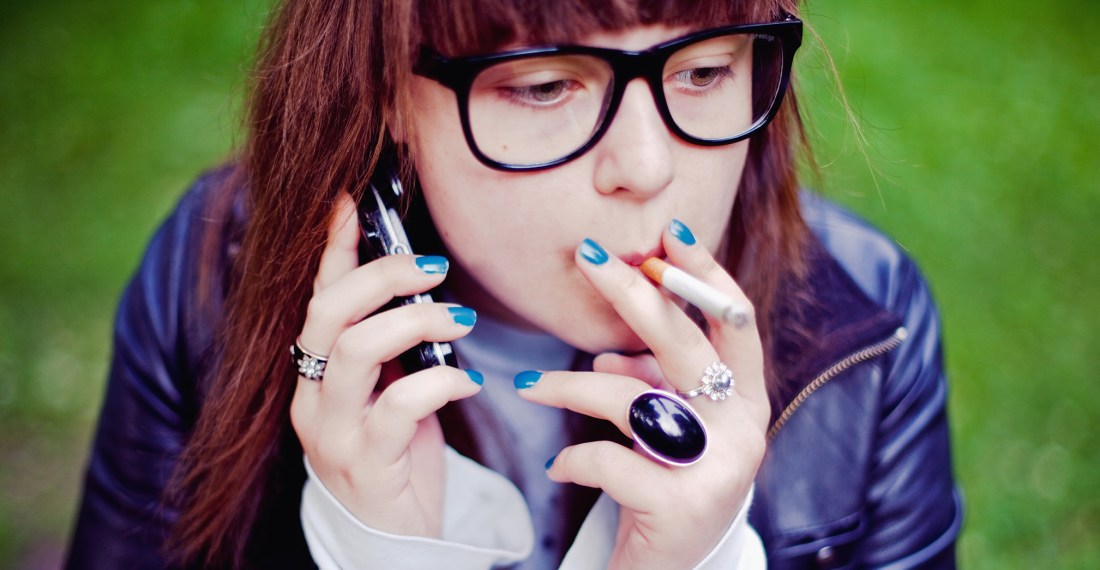 girl with glasses with black frames on the phone and smoking a cigarette