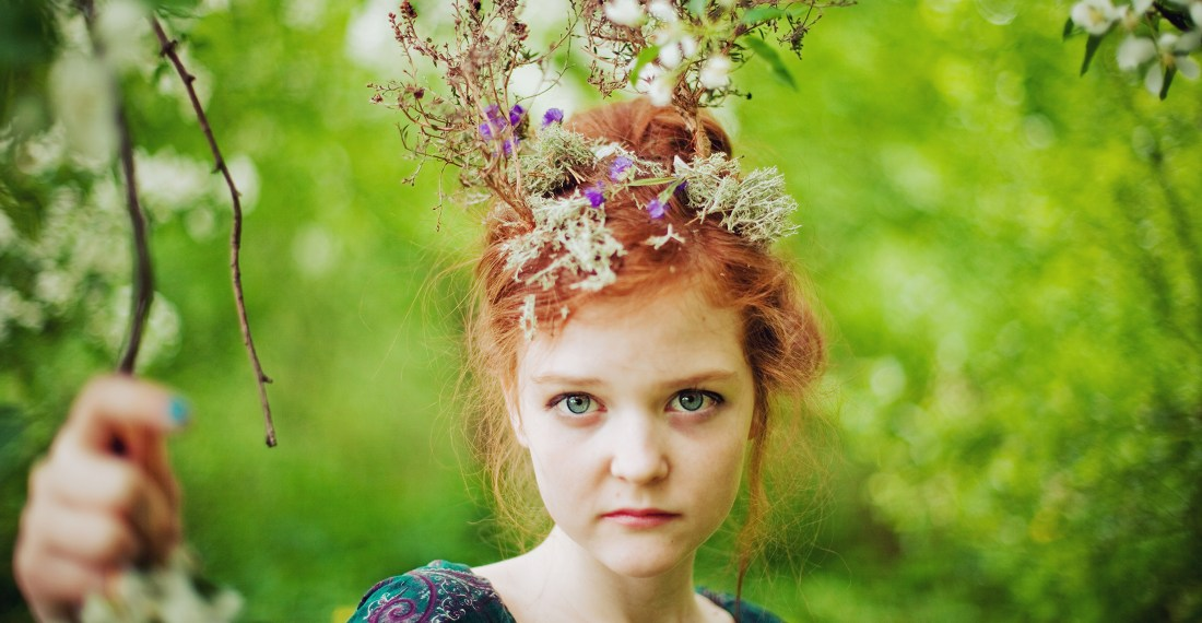 redhead girl with a miniature trees on her haid in a forest