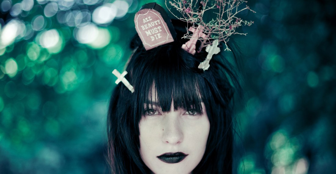 girl with black hair with miniature graveyard on her head