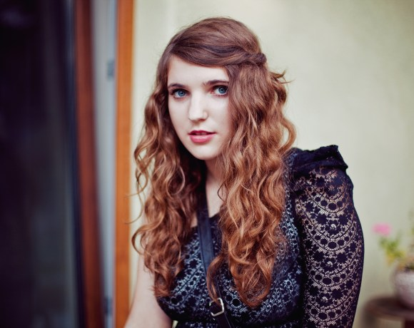 girl with brown curly hair and black lace dress
