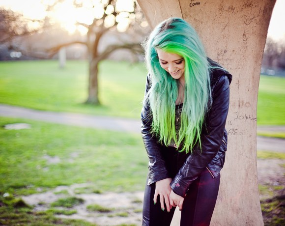 alternative girl with blue green hair smiling in a park at sunset