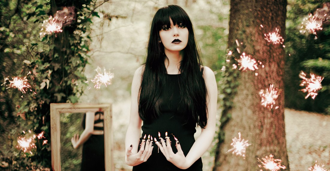 girl with black hair in a forest with a mirror behind her and flames coming out of her fingers and sparkles surrounding her