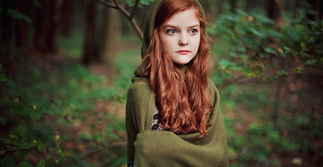 redhead cute girl in a green elvish cape in a forest