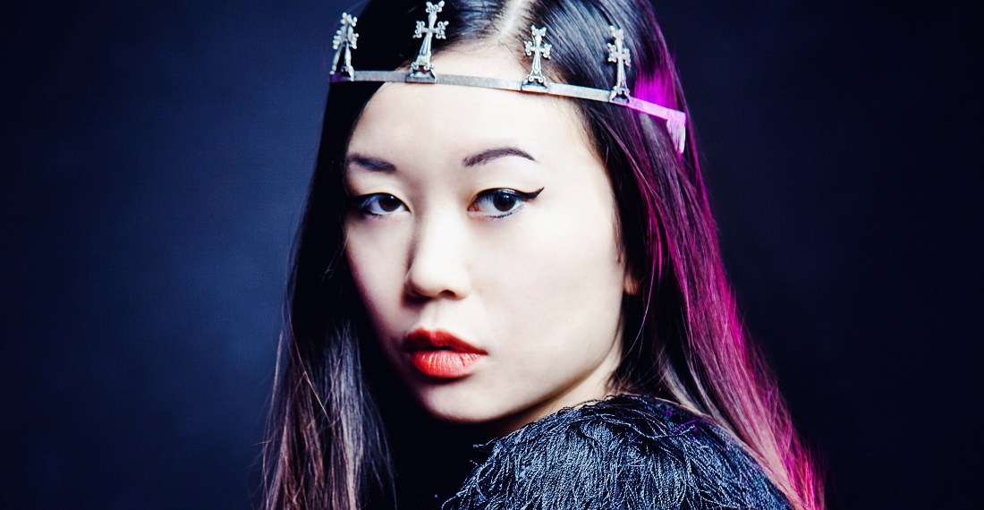 asian model in a studio with black background and black top and a cross crown on