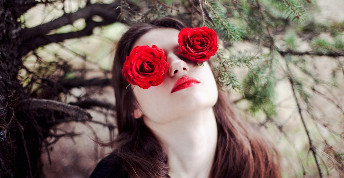 girl in the forest by a tree with red roses on her eyes