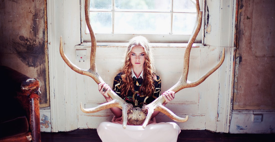girl sitting in a derelict house with big antlers