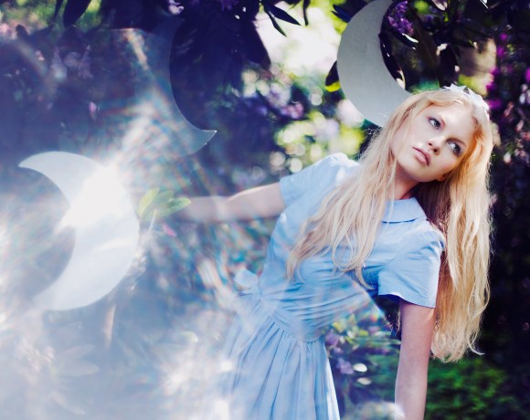 dreamy magical image of a girl dressed in blue in a garden between moons