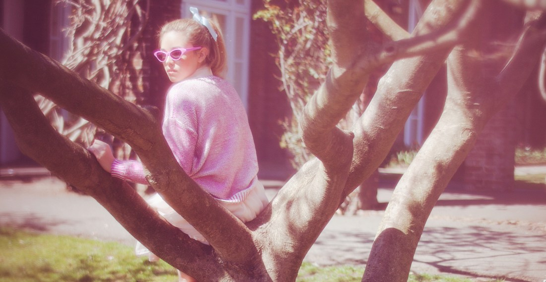 dreamy vintage image of a girl dress in pink with sunglasses in a tree