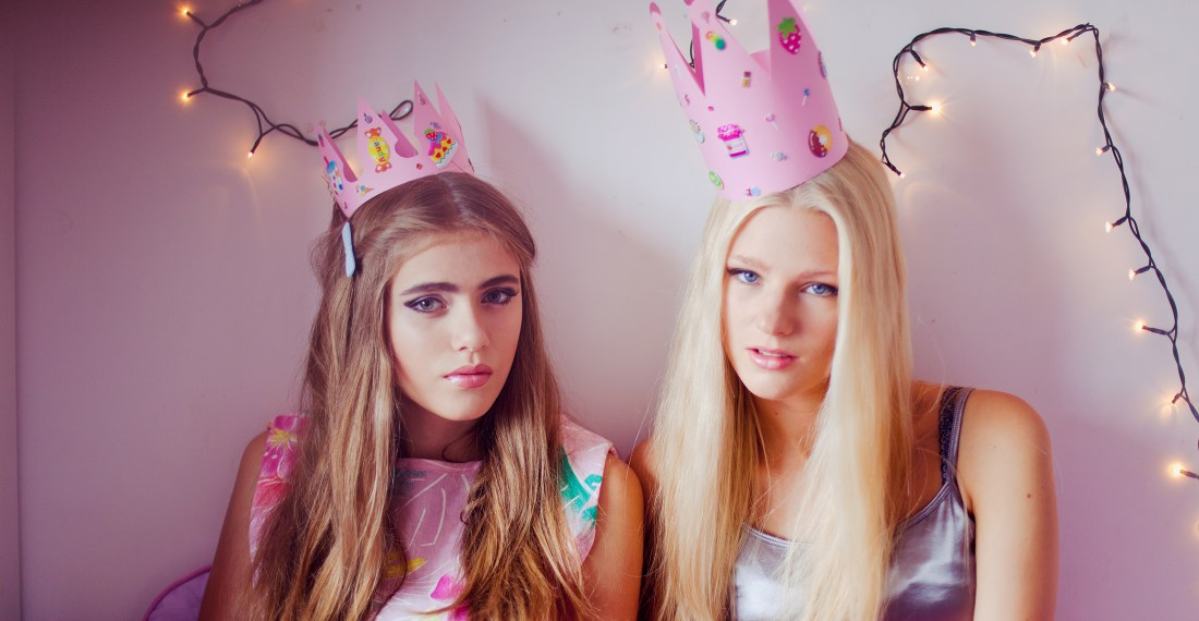 two girls in pink crowns with stickers and fairy lights behind them