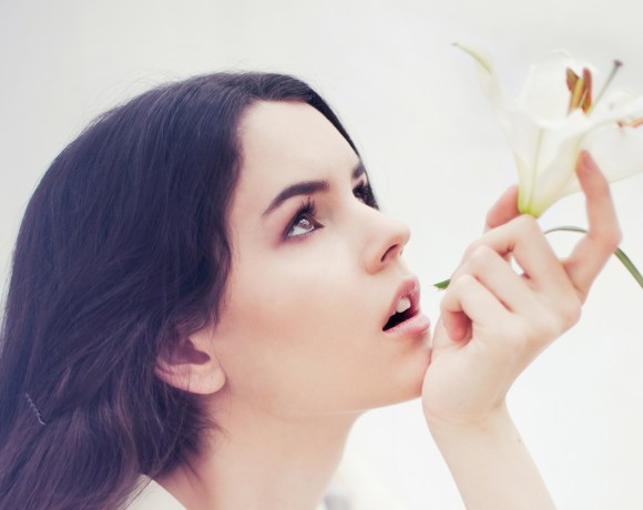 portrait of a dark haired girl drinking out of a lily