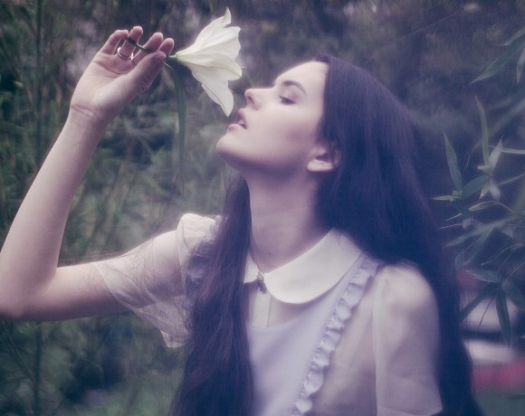 dark image of a dark haired girl drinking from a lily