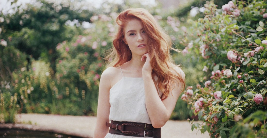 film picture of a redhead girl in a white dress in a garden