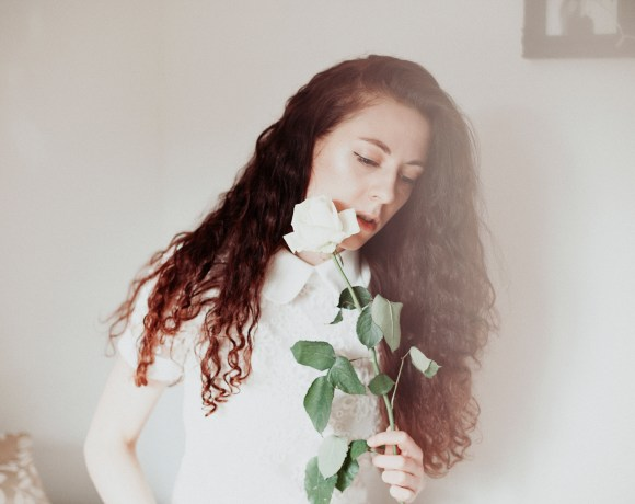 brunette girl with curly hair in her bedroom in a white lace top holding a white rose
