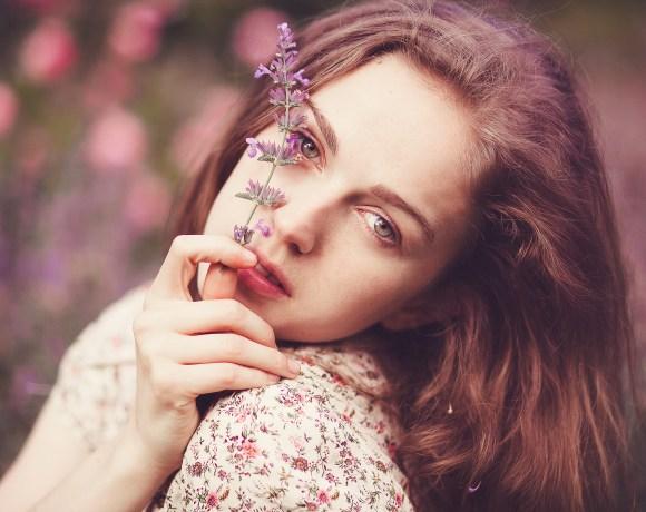 dreamy portrait of a girl holding a purple flower in a garden
