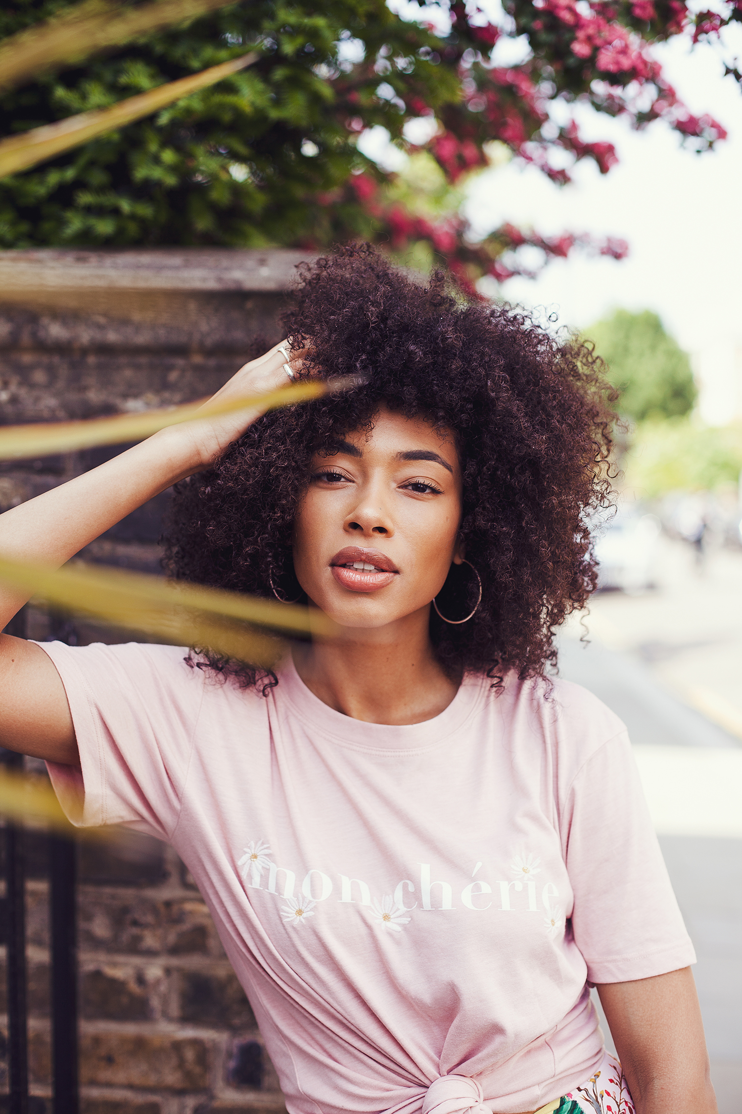 Portrait of fashion blogger Lesley in Notting Hill by Ailera Stone. Wearing a pink top among plants