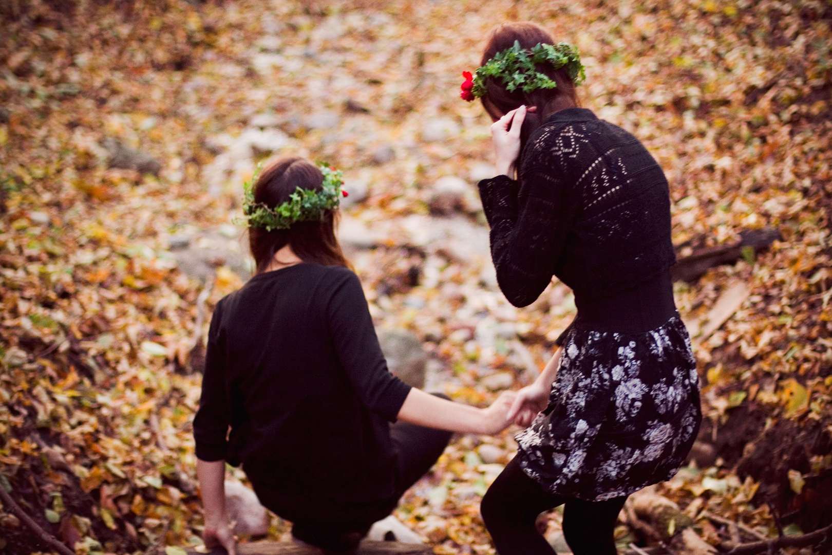 girls in flower crowns in a forest climbing by Ailera Stone