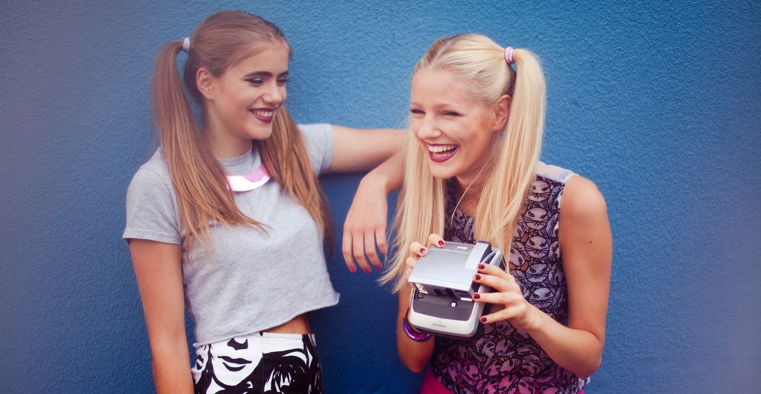 Fashion photoshoot behind the scenesm two girls in front of blue wall with a polaroid - by London based photographer Ailera Stone.