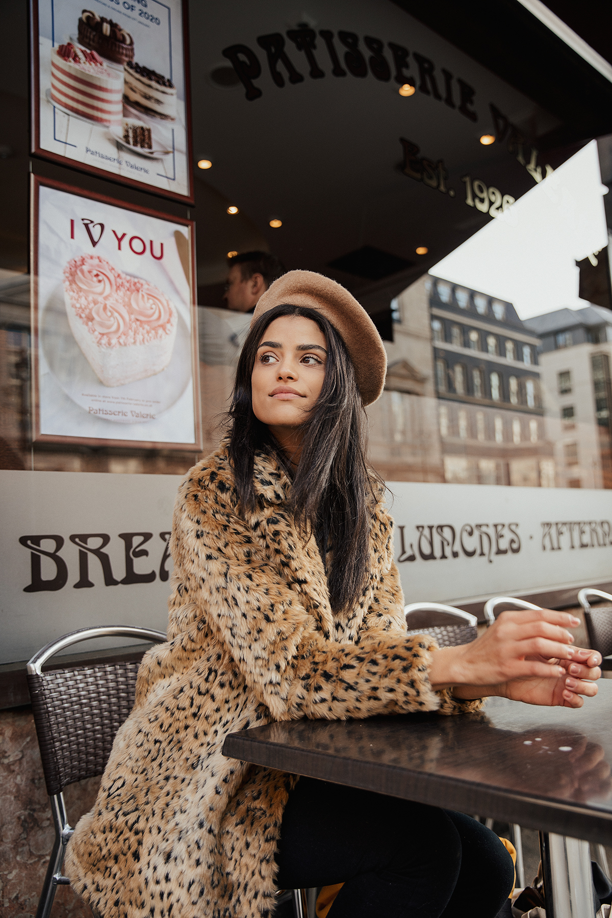 Parisian style photoshoot by London photographer Ailera Stone, dark haired model sitting in a french cafe in a beret and a leopard coat