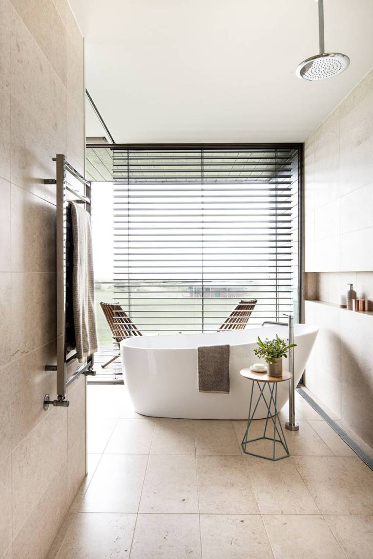 To complement the natural beauty outside, this bathroom incorporates earth tones, organic shapes, and an open layout