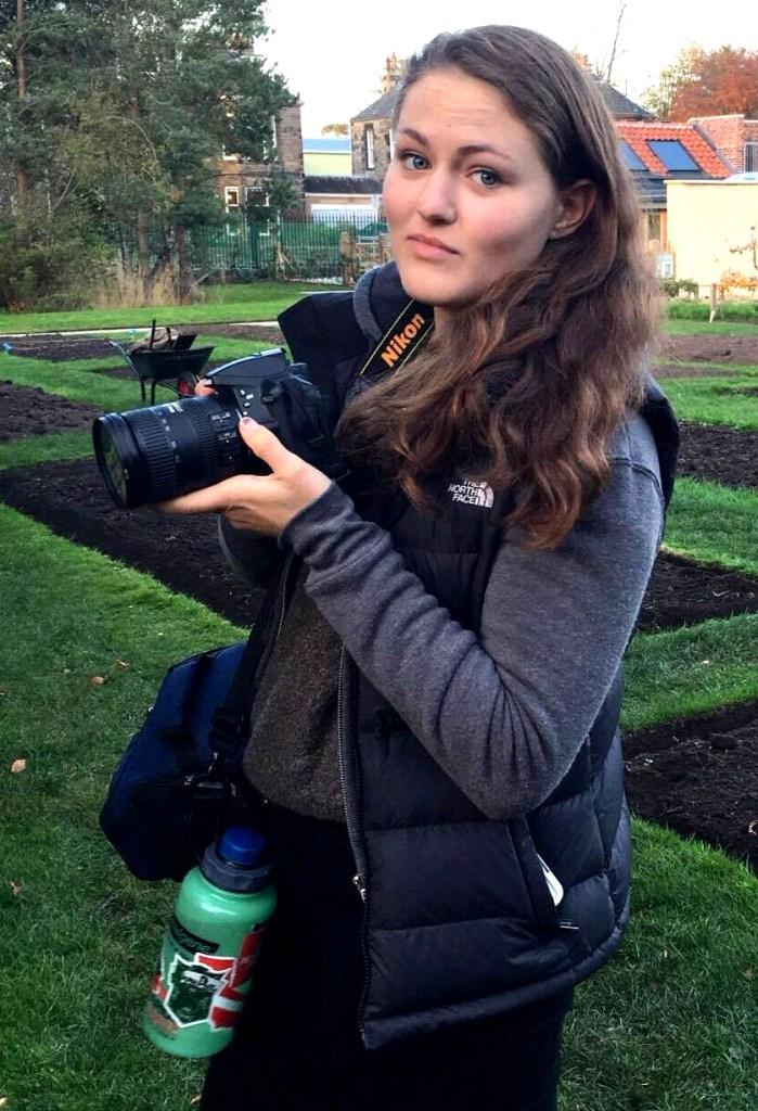 Emma Marsano, standing in a garden, holding a camera