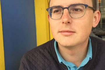 Patrick Johnson-Whitty, headshot, wearing a light blue collared shirt and grey glasses