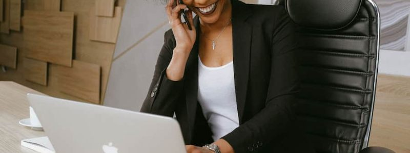 Female smiling on a phone call and typing on a laptop