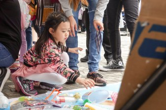 The girl tries to distinguish the possible recyclable materials among all plastic products and put them in the right place.