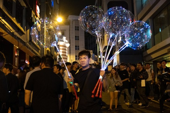 A saleman holding several LED balloons was trying to find customers in Lan Kwai Fong at night time.