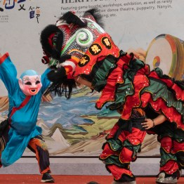 Man interacting with the lion as a clown with a funny mask in order to make the lion dance