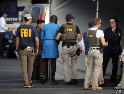 Federal agents hold a detainee, second from left, in downtown Los Angeles after predawn raids that saw dozens of people arrested in the L.A. area, Aug. 22, 2019, Most of the defendants are Nigerian nationals.