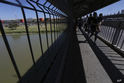 FILE - People walk back to Mexico on the Americas International Bridge, a legal port of entry which connects Laredo, Texas in the U.S., with Nuevo Laredo, Mexico, July 18, 2019.