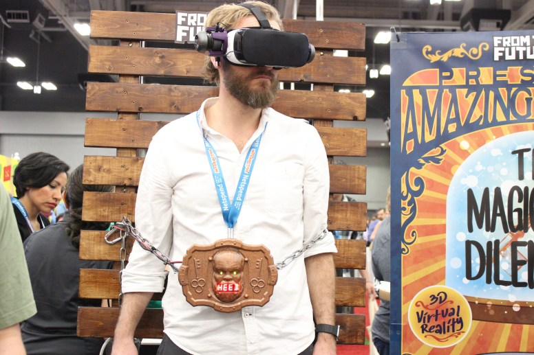 A man is completing a Houdini-like escape trip via VR at the Denton booth. / Photo by Dana Summers