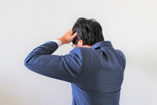 頭に手を置く男性