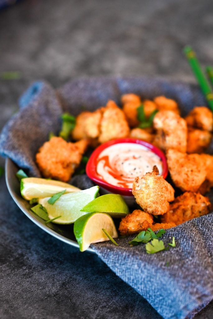 close-up image of buffalo cauliflower wings with lime wedges.
